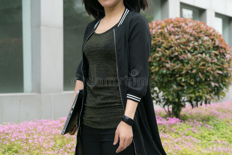 A woman is holding laptop computer while walking stock images