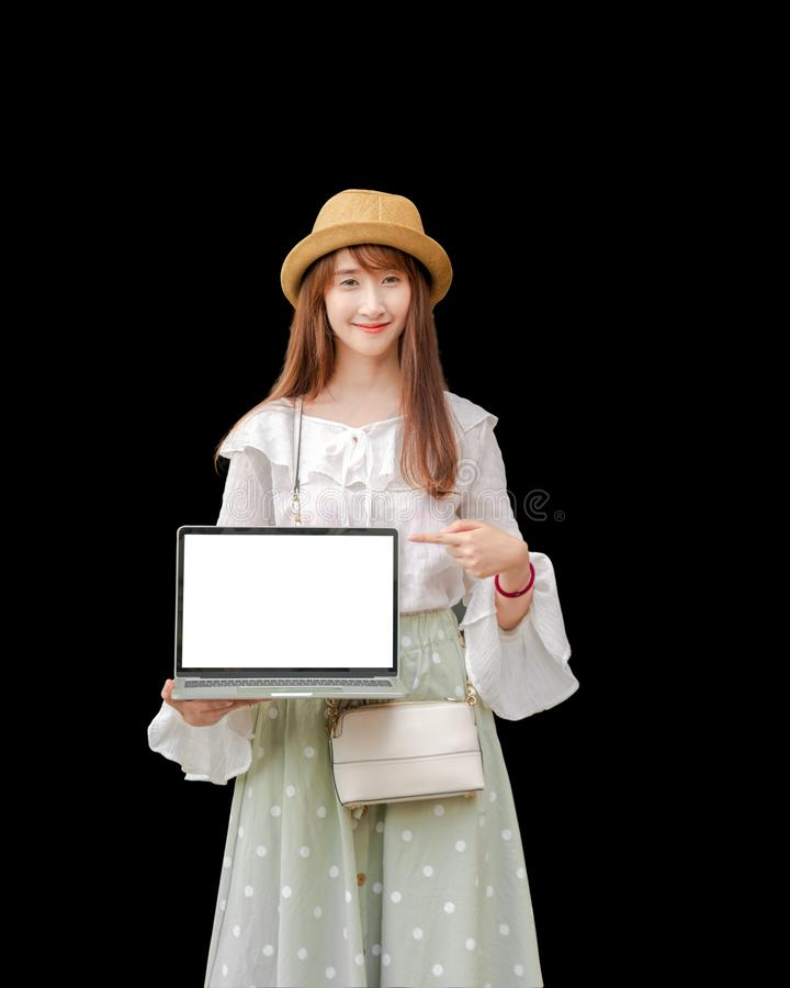 Asian woman holding laptop is white screen, black background royalty free stock photo