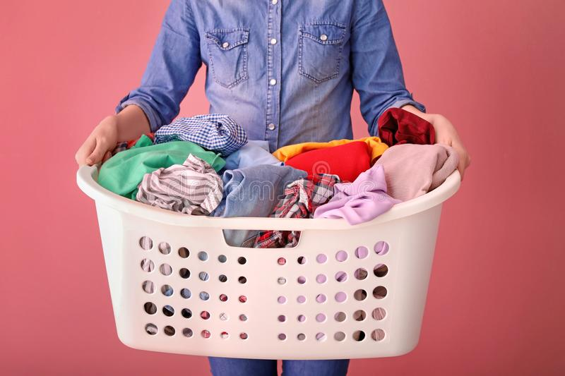 Woman holding laundry basket with dirty clothes royalty free stock image