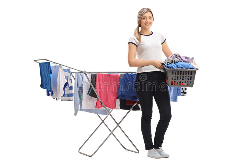 Woman holding laundry basket in front of clothing rack dryer stock images