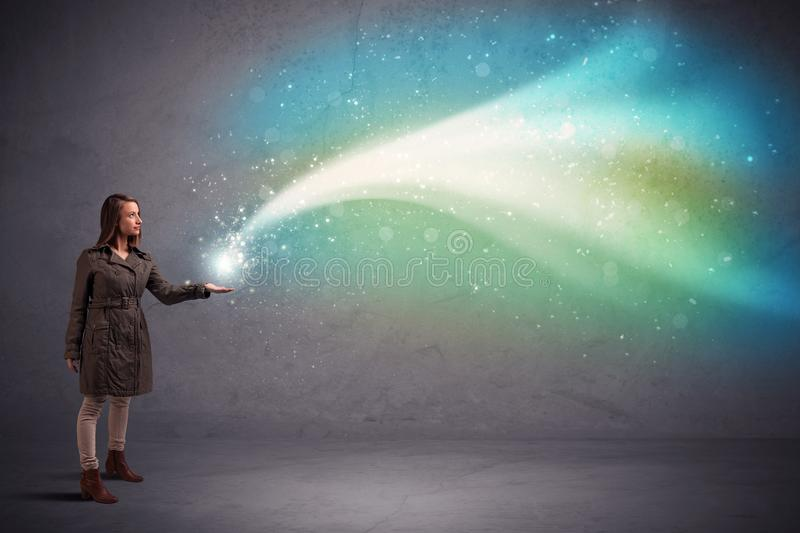 Woman holding light. Caucasian woman holding blue, white, green coloured stria of light royalty free stock photos