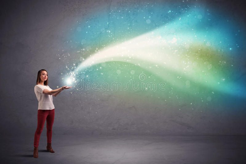 Woman holding light. Caucasian woman holding blue, white, green coloured stria of light royalty free stock images