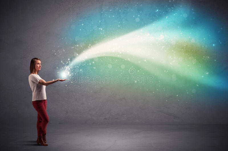 Woman holding light. Caucasian woman holding blue, white, green coloured stria of light stock photo