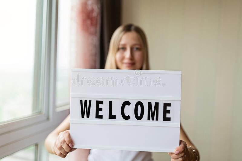 Woman holding lightbox with Welcome in hands. End of covid-19 quarantine. Hotel, restaurant, cafe, local shop, service owner. Woman holding lightbox with word stock images