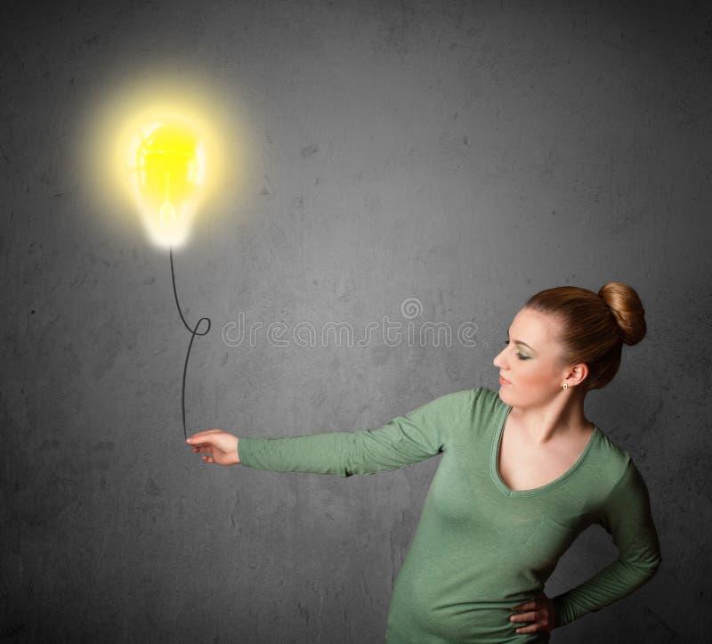 Woman holding a lightbulb balloon. Young woman holding a lightbulb balloon royalty free stock image