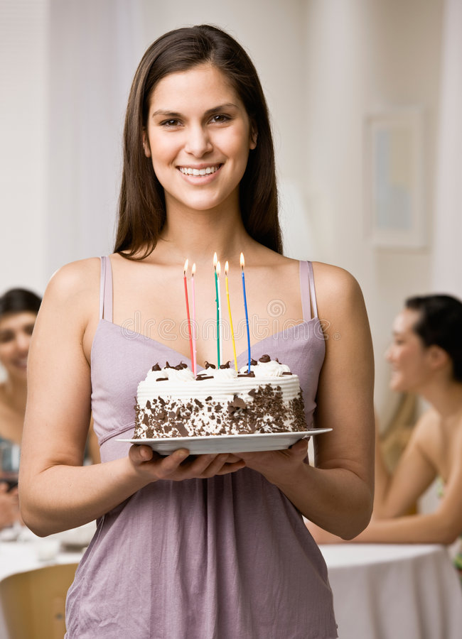 Woman holding lighted birthday cake. Generous woman holding lighted birthday cake about to surprise friends royalty free stock images