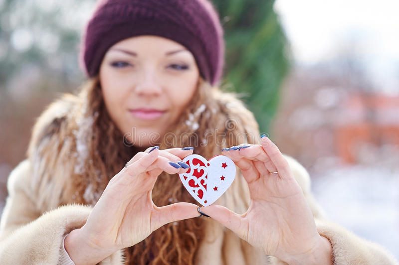 Woman holding a little heart in winter park.  stock image