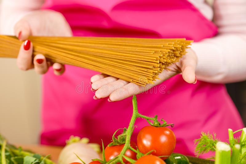 Woman holding long pasta. Macaroni ready to cook spaghetti. Healthy food concept royalty free stock photos