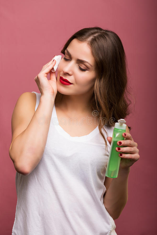 Woman holding a lotion and a cotton pad. Woman cleaning her face with a lotion and a cotton pad stock photos