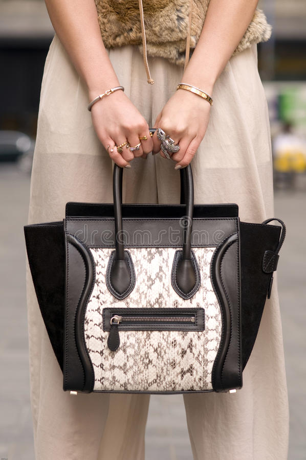 Woman holding purse, handbag with rings on fingers. Woman holding luxury handbag, with rings on her fingers and bracelets stock image