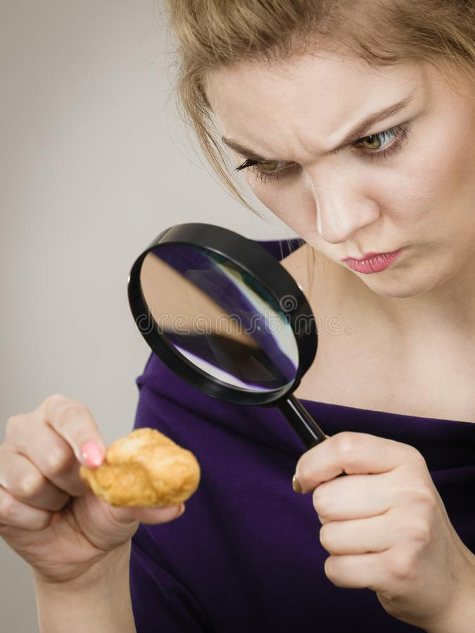 Woman holding magnifying glass investigating bread. Blonde woman holding magnifying glass investigating piece of bread. Gluten products, food ingredients and stock images