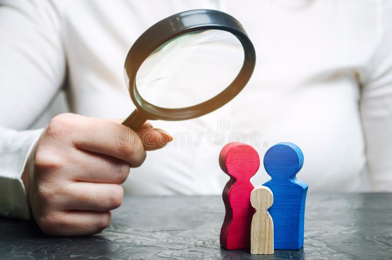 A woman is holding a magnifying glass over the wooden figures. Studying family composition, needs and health. Popularization of stock photo