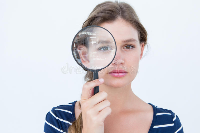 Woman holding magnifying glass. On white background stock photography