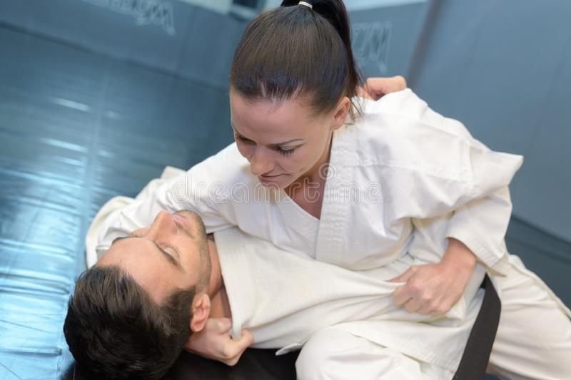 Woman holding man in karate hold on floor stock photography