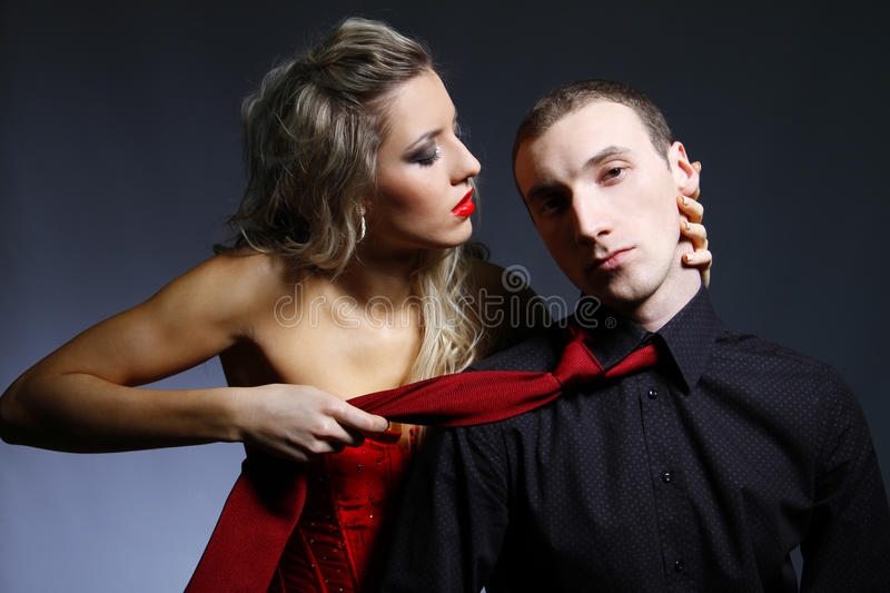 Woman holding a man for a tie. Beautiful woman holding a man for a tie and leaning to kiss him stock photography
