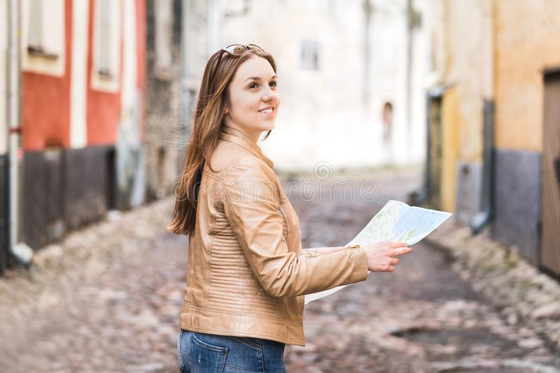 Woman holding map in city street or old town. royalty free stock images