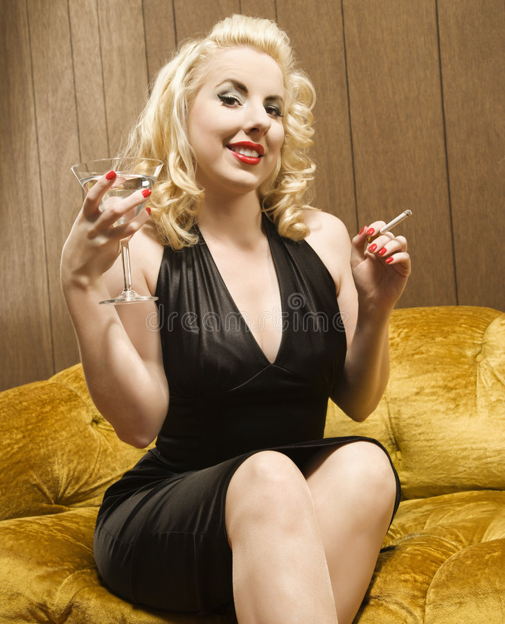 Woman holding martini. Attractive Caucasian woman holding a martini and cigarette royalty free stock photo