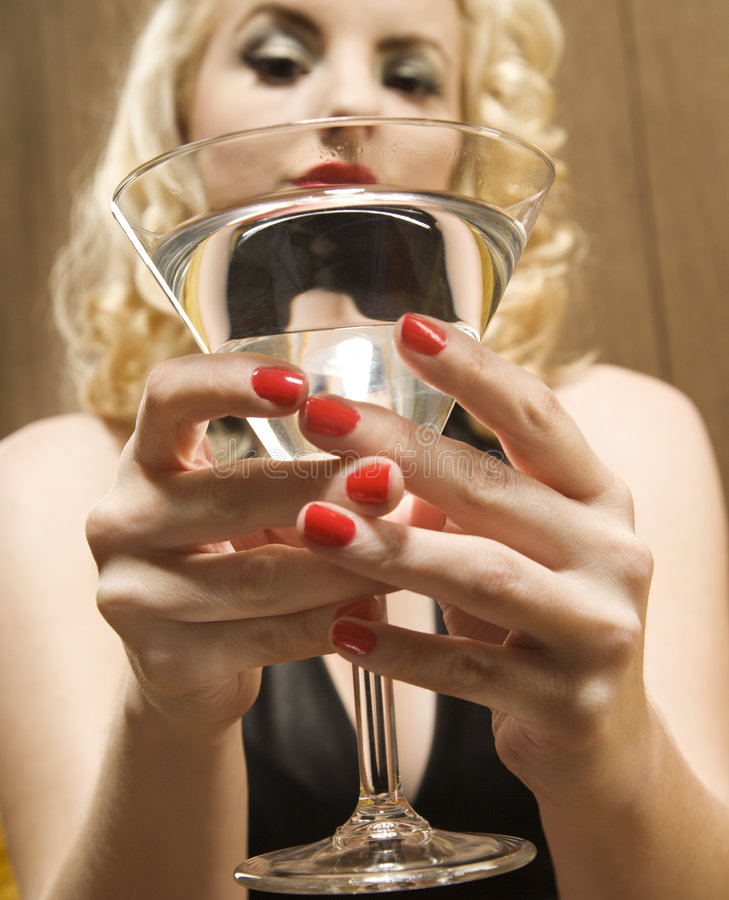 Woman holding martini. Attractive Caucasian woman holding a martini out to viewer royalty free stock photos