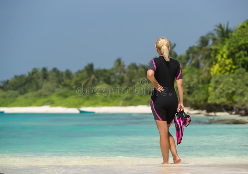 Woman holding mask and flippers for swimming on tropical beach stock image