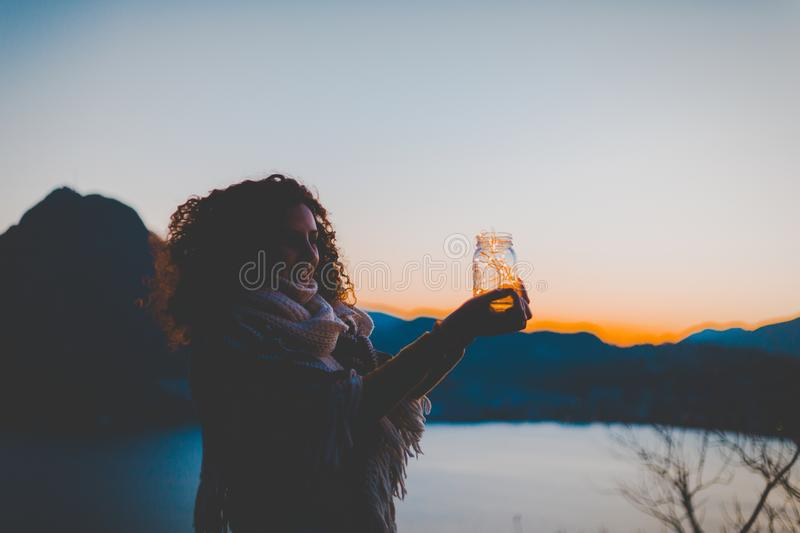 Woman Holding Mason Jar With String Light With Lake and Mountain over View during Golden Hour royalty free stock images