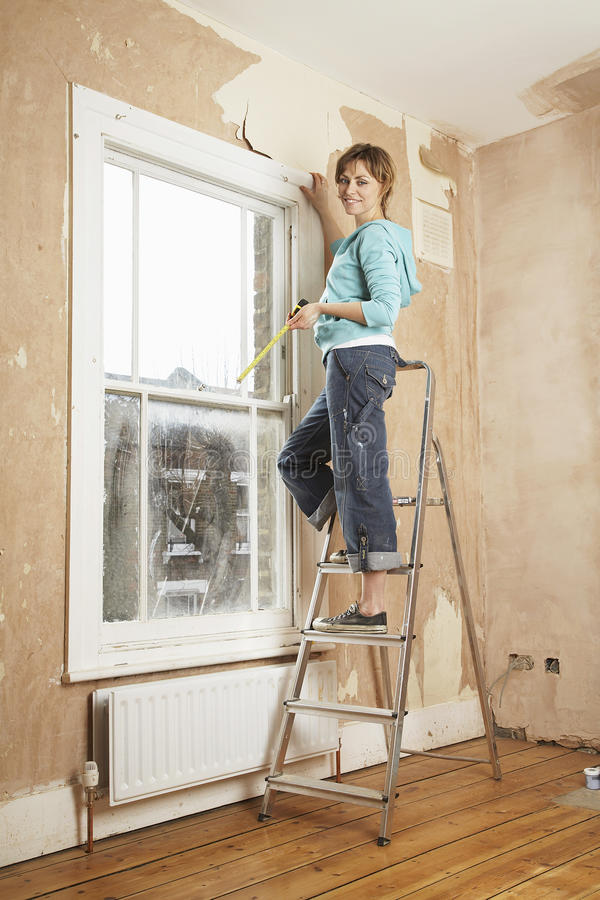 Woman Holding Measure Tape While Standing On Step Ladder. Portrait of woman holding measure tape while standing on step ladder in unrenovated house royalty free stock photography