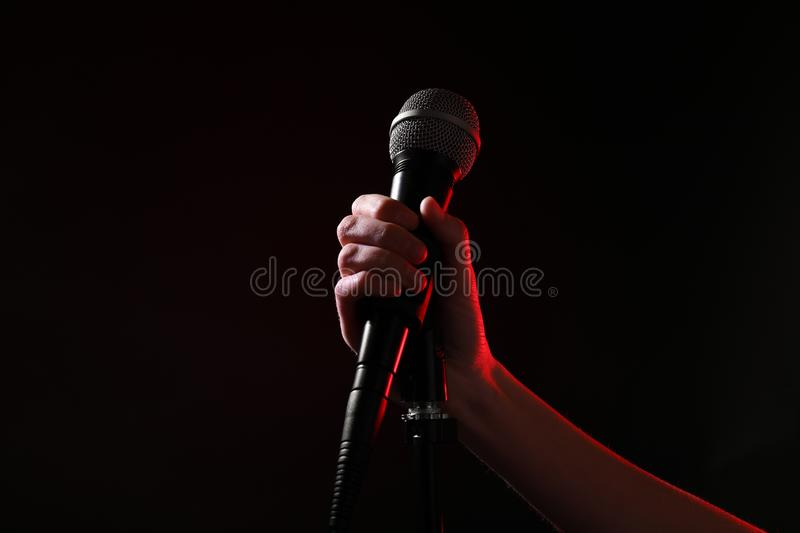 Woman holding microphone on black background. Closeup royalty free stock photo