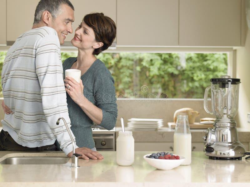 Woman Holding Milkshake While Looking At Husband In Kitchen. Happy women holding milkshake while looking at husband at kitchen counter royalty free stock image