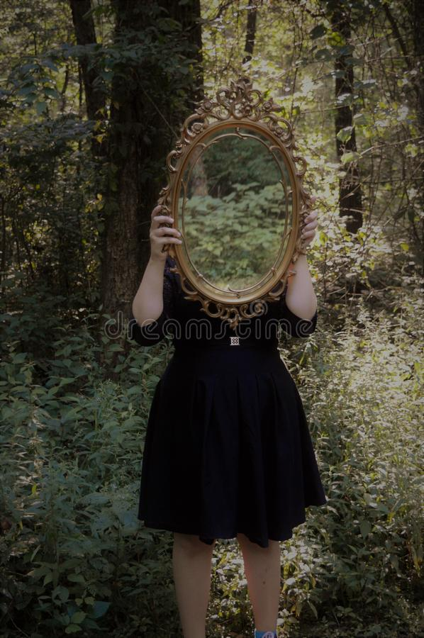 Woman Holding Mirror Against Her Head in the Middle of Forest royalty free stock image