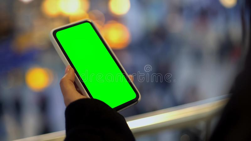 Woman holding mobile phone with green screen, standing in shopping center, ad stock image