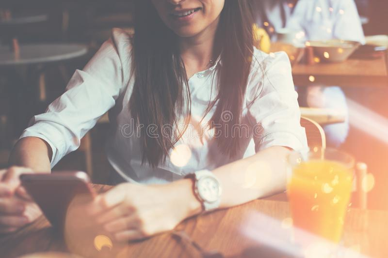 Woman holding mobile phone in hands, reading news feed from the internet, breakfast of handsome business lady in cafe stock photos