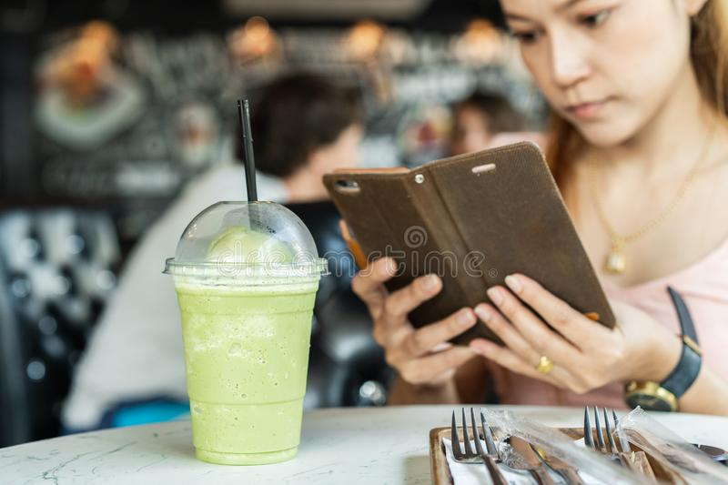 Woman holding mobile smart phone taking photo to green tea frappe. In cafe royalty free stock images