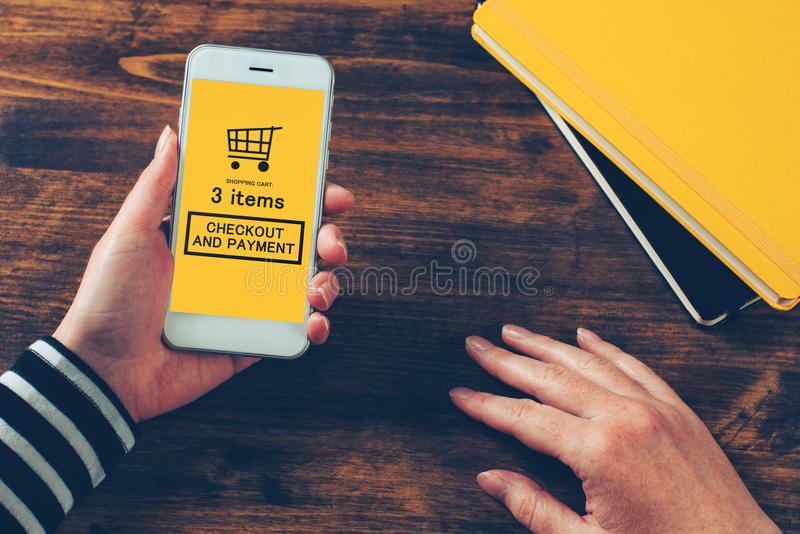 Woman holding modern mobile phone with online shopping application stock photography