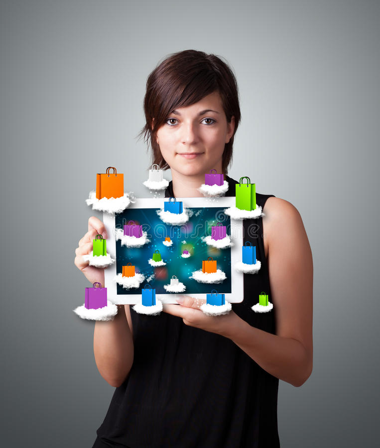 Download Woman Holding Modern Tablet With Colorful Shopping Bags On Cloud Stock Photo - Image: 28655942
