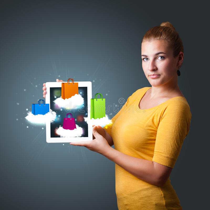 Download Woman Holding Modern Tablet With Colorful Shopping Bags On Cloud Stock Image - Image: 29074073