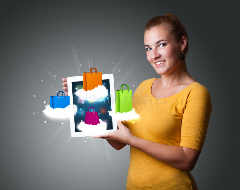 Woman holding modern tablet with colorful shopping bags on cloud. Beautiful woman holding modern tablet with colorful shopping bags on clouds stock image