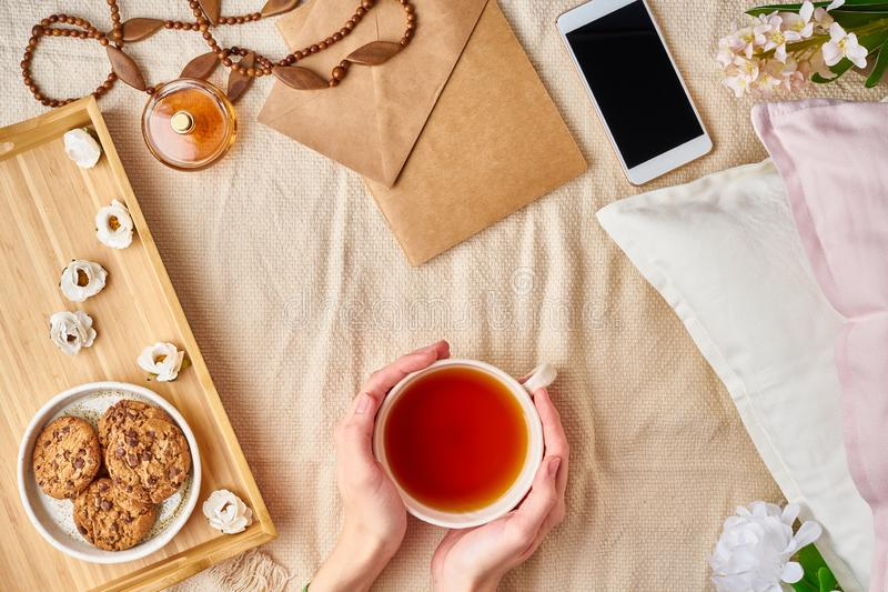 Woman holding mug of hot tea. Lazy cozy morning in bed. Flat lay woman accessories with letter, envelope, smartphone, perfume stock photos