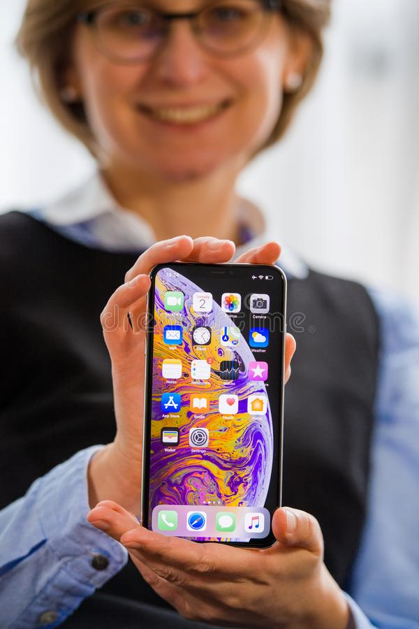 Woman holding new iPhone Xs in hand home screen royalty free stock image