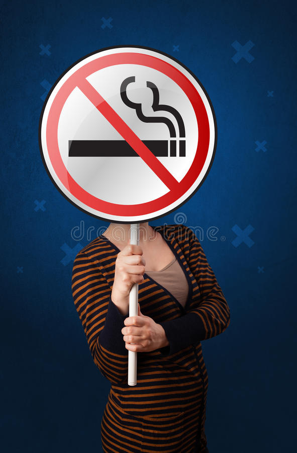 Woman holding no smoking sign. Casual young woman holding round sign with no smoking graphic stock images