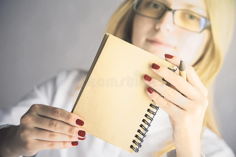 Woman holding notepad. Portrait of young caucasian woman holding empty spiral notepad and pen on blurry background. Mock up stock photography