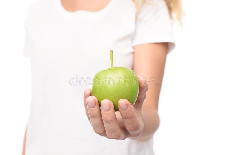 Woman holding and offering green apple, closeup stock images
