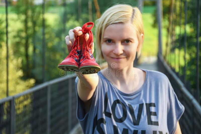 Woman holding in one extended arm small red baby shoes stock photos