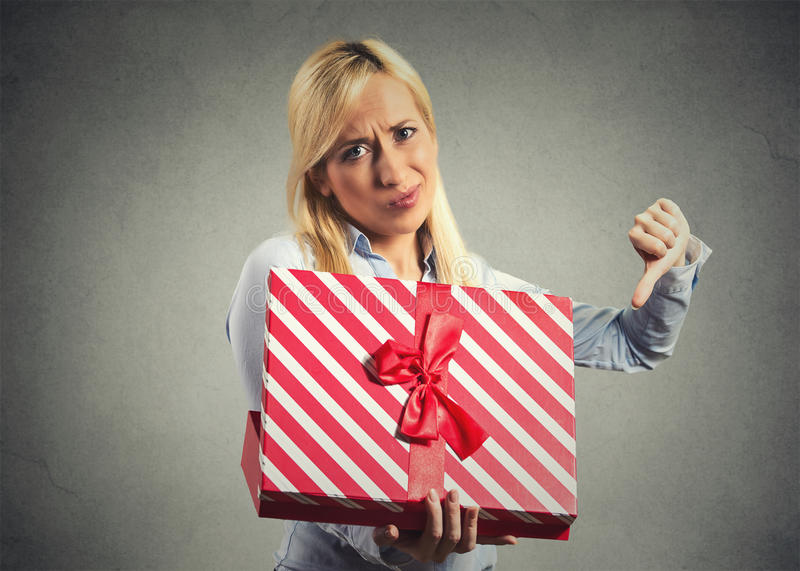 Woman holding, opening gift box, displeased with what she received. Closeup portrait young woman holding, opening gift box, displeased, disgusted with what she stock photo