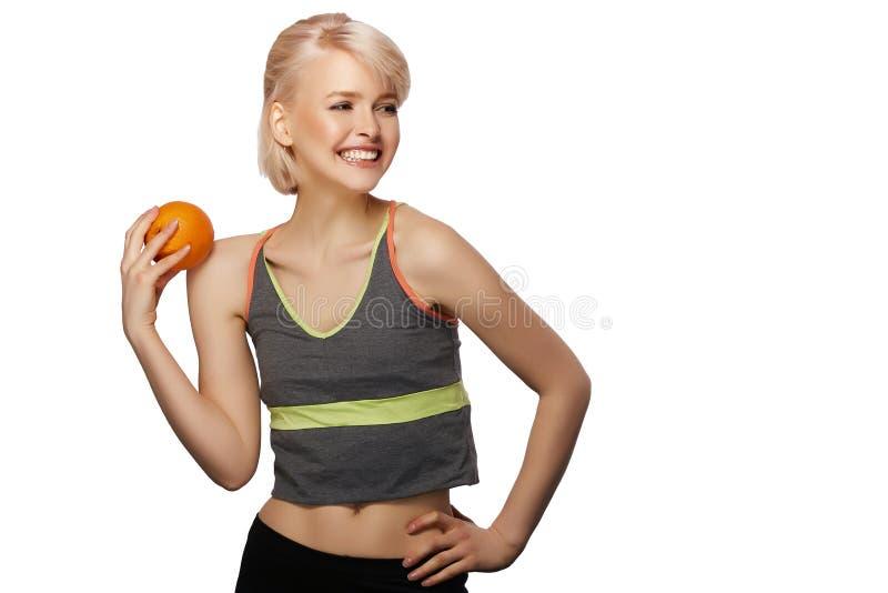 Woman holding orange. Happy smiling slim woman holding the orange, studio portrait isolated on white background, healthy lifestyle concept stock images