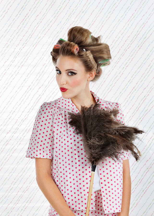 Woman Holding an Ostrich Feather Duster. Portrait of young woman with hair curlers puckering while holding an ostrich feather duster stock image