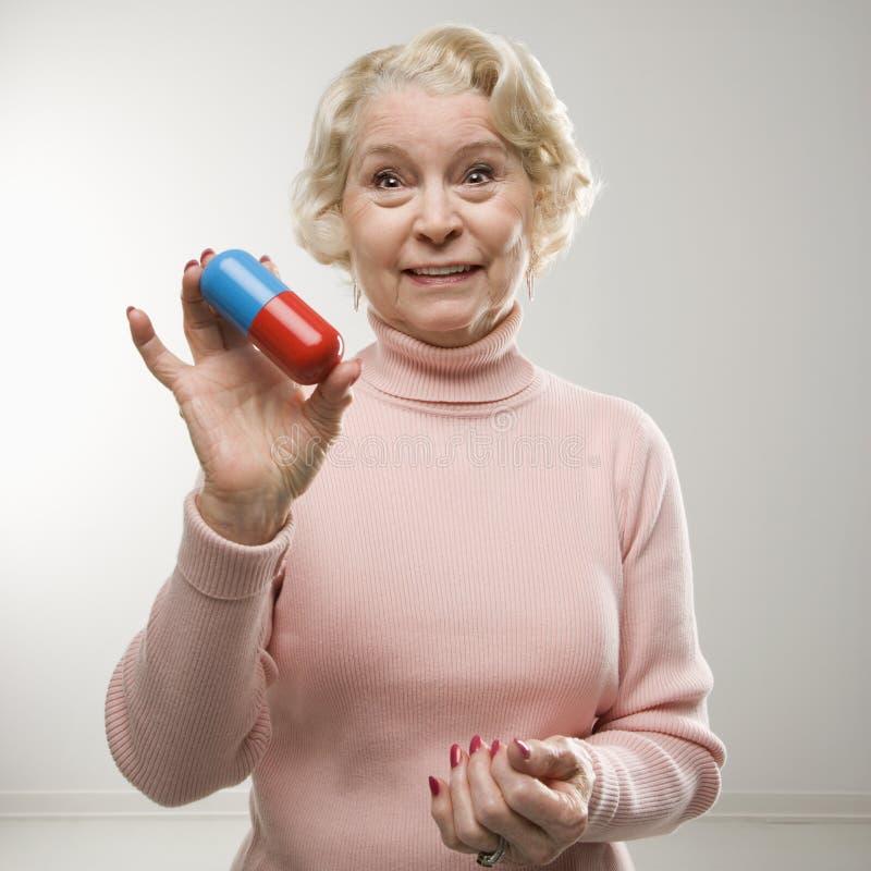 Woman holding oversized pill.