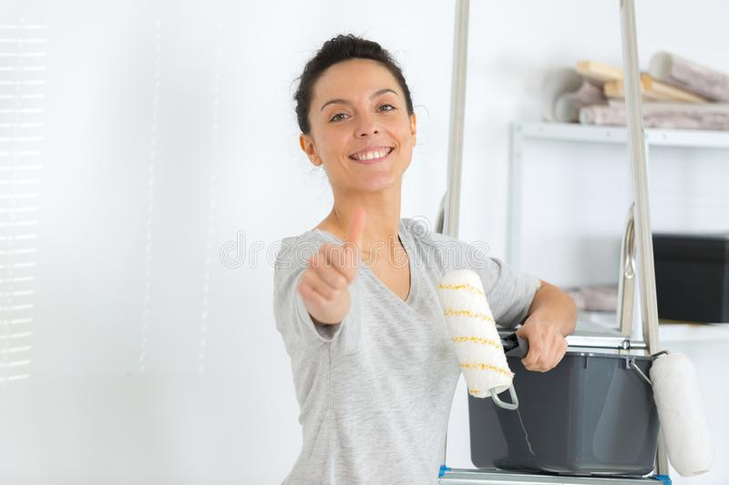 Woman holding paint roller making thumbs up gesture royalty free stock photography