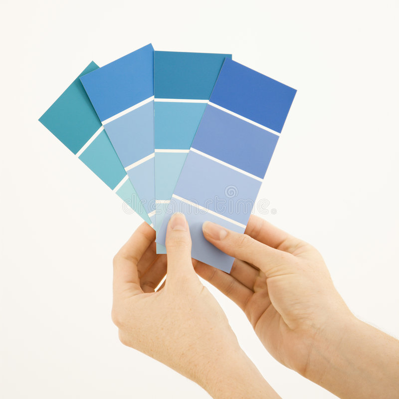 Woman holding paint swatches. Caucasian female hands holding paint color swatches stock photos