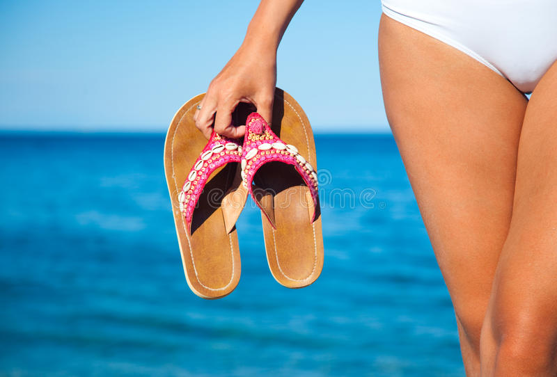 Woman holding a pair of flip flops in the water. Woman holding flip flops on the shoreline stock image