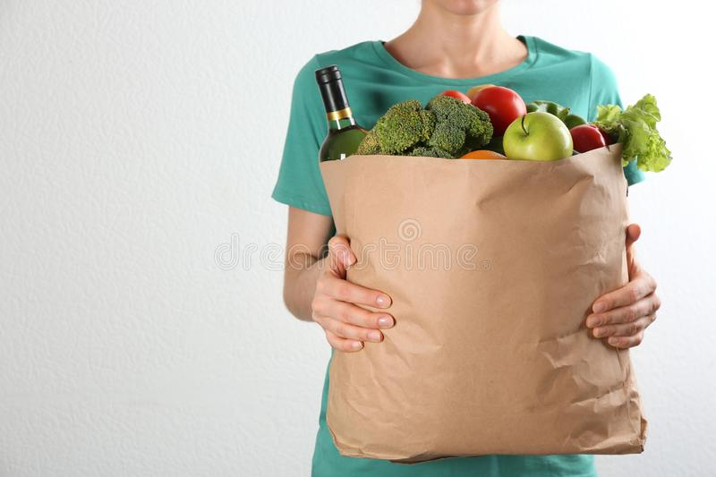 Woman holding paper bag with different groceries near white wall. Space for text. Woman holding paper bag with different groceries near white wall, closeup view stock photo