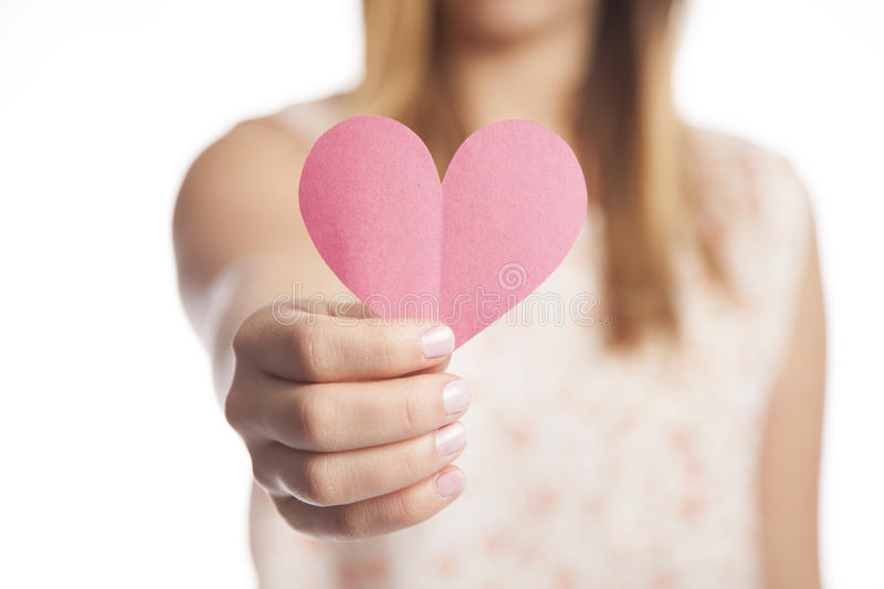 Woman Holding Paper Heart. A young woman holds out a cut out construction paper heart royalty free stock photos